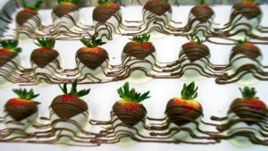 tray of chocolate covered strawberries drizzled with chocolate