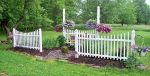 garden with white picket fence and bench
